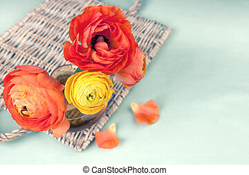 Colorful ranunculus flower on vintage wicker tray