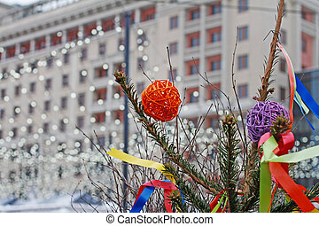 """Colorful rattan balls hanging on a Christmas tree with ribbons on background of christmas garland at Russian national festival """"Shrove"""" in Moscow"""