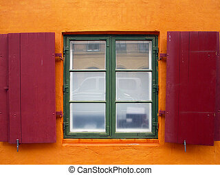 Colorful red shutters on a window.