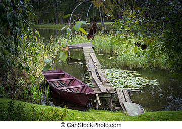 Colorful red wooden rowboat in a tranquil lake