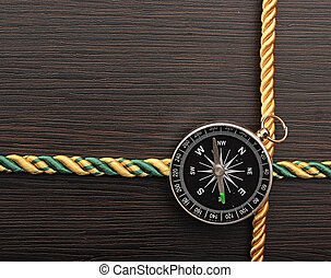 colorful rope frame with compass on wooden background