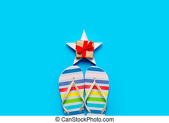 colorful sandals and beautiful gift on star shaped toy on the wonderful blue background