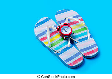 colorful sandals and cute small alarm clock on the wonderful blue background