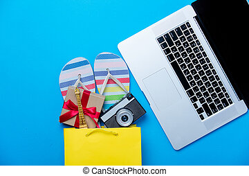 colorful sandals, camera and gift in shopping bag and cool laptop on the wonderful blue background