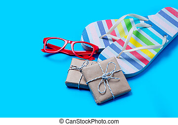 colorful sandals, glasses and cute gifts on the wonderful blue background