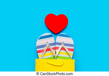 colorful sandals in cool shopping bag and heart shaped toy on the wonderful blue background