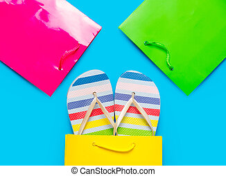 colorful sandals in cool shopping bag near other beautiful shopping bags on the wonderful blue background
