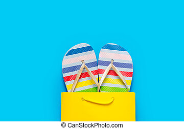 colorful sandals in cool shopping bag on the wonderful blue background