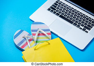 colorful sandals in shopping bag and cool laptop on the wonderful blue background