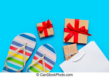 colorful sandals, shopping bag and beautiful gifts on the wonderful blue background