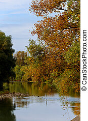 Colorful scenic idyllic autumn landscape at a river shore with trees reflecting on the water on a sunny autumn day