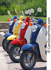 Red, yellow and blue scooters parked in a row.