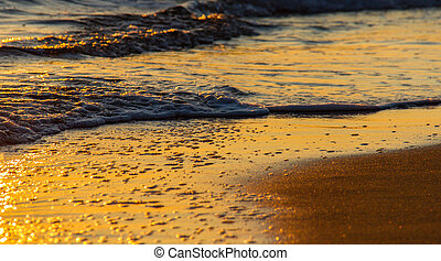Colorful shapes of breaking waves on sandy shore at sunset