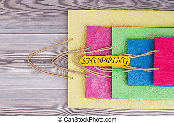 Colorful shopping bags on wooden background.