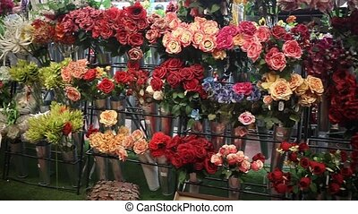 Colorful showcase of flower shop with large assortment of artificial flowers. High quality FullHD footage