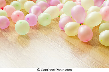 Colorful small balloons lying on wooden floor