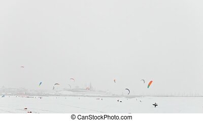 Colorful snow-kites over the ice river in front of city at blizzard cloudy day, winter extremal sport
