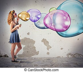 Girl has fun making colorful soap bubbles