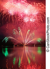 Colorful spectacular fireworks with reflections in the water