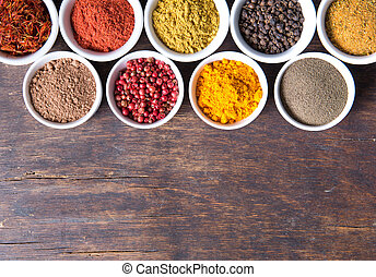colorful spices in ceramic containers on a dark background
