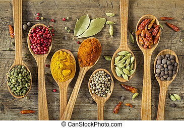 Colorful spices in wooden spoons