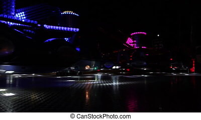 Colorful spinning wheel in amusement park at night. - Fast...