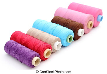 Colorful spools of thread on white background