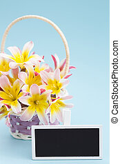 Colorful spring flower bouquet, in wicker basket and blank blackboard sign for text, on blue background.