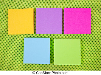 Colorful sticky notes on green fabric background.