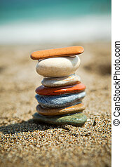 Colorful stone stacks on a pebble beach