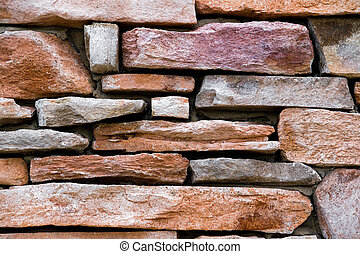 A wall composed of beautiful, colorful rectangular sandstone.