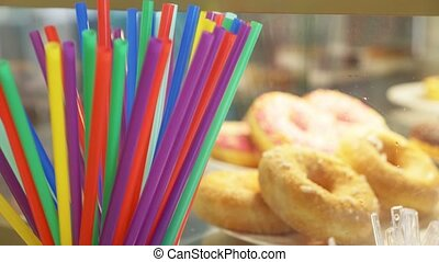 colorful straws for drinks on the background of donuts in a...
