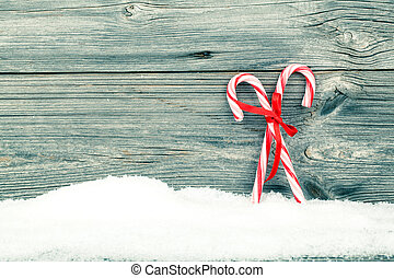 Colorful striped red and white Xmas candy canes with winter snow