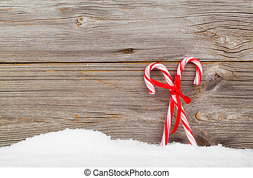 Colorful striped red and white Xmas candy canes with winter snow on wooden boards, with copyspace