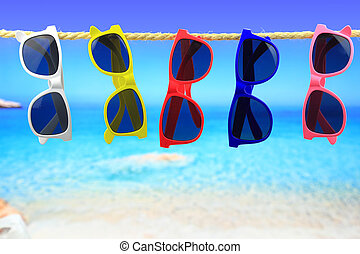 Colorful Sunglasses hanging on a rope in front of the sea