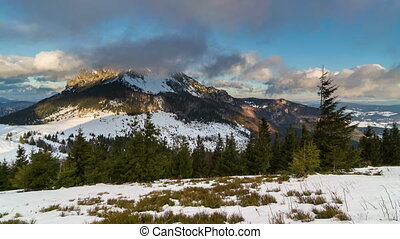 Colorful sunny winter day in mountain with clouds flying over peak time lapse