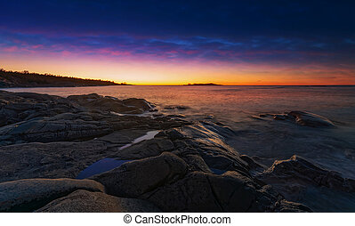 Colorful sunrise at coastline with orange and blue dark dramatic sky