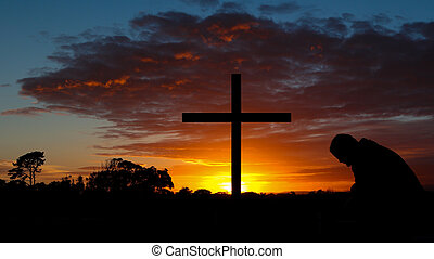 Colorful Sunrise Cross - Man in pray before a cross at...