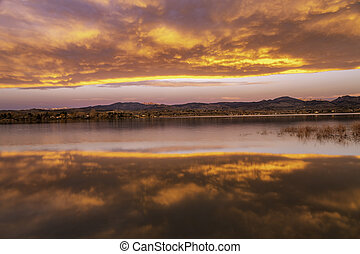 Colorful Sunrise or Sunet reflecting in a lake along the Colorado Mountain Front range