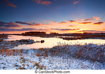 colorful sunrise over river in winter