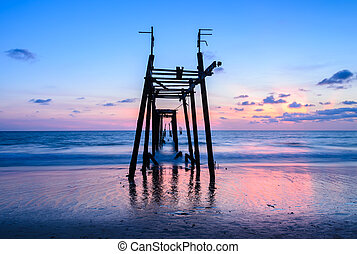 Colorful sunset beach with abandoned wooden pier