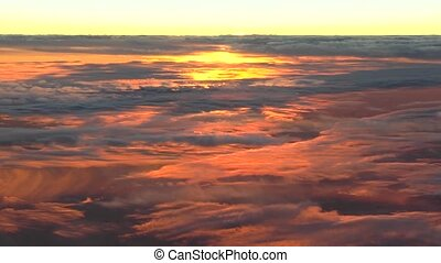 Flying above the clouds; colorful high altitude sunset clouds. Unique, actual, aerial footage.