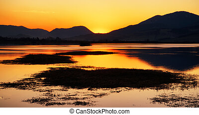 Colorful sunset over lake and mountains
