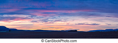 Colorful sunset over plowed fields in Northern Bohemia in the Czech Republic