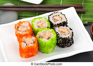 Colorful sushi maki with tobiko on bamboo mat