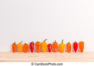 Colorful sweet peppers on wooden surface