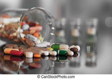 Colorful tablets with capsules and pills on background