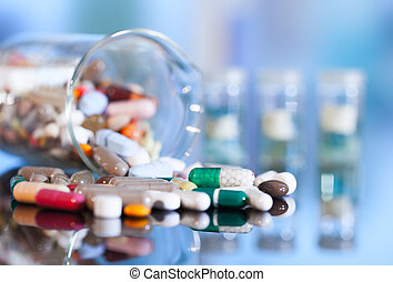Colorful tablets with capsules and pills on blue background