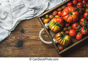 Colorful tomatoes of different sizes and kinds in dark wooden tray over rustic background, copy space