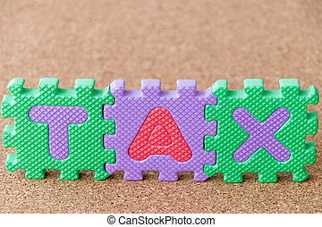 Colorful toy foam alphabet in word tax on cork board background